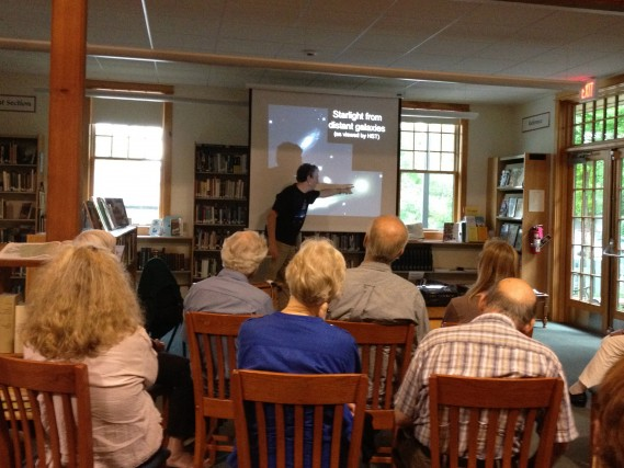 """Community members attend a talk titled """"Why is it dark at night?"""" at the Putney Public Library with Tom Geballe"""